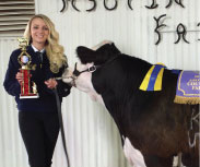 Young girl standing with a cow, holding a trophy.