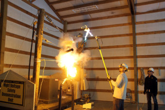 Lineman performing an electrical safety demonstration showing how power lines can catch fire.
