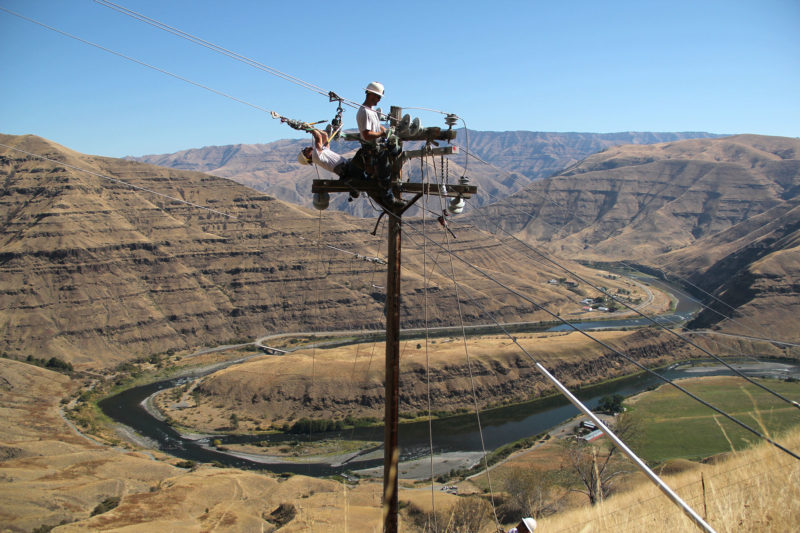 linemen working on power pole high above the landscape
