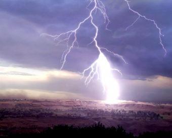 Lightning striking down on the ground.