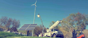 Linemen in a bucket truck going up to a windmill above a solar panel on the ground.